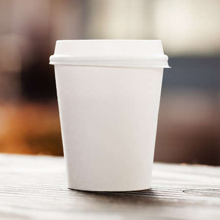 disposable: Disposable coffee cup on windowsill with city in background. Stock Photo