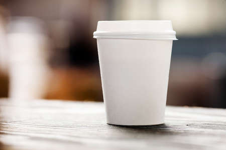 coffee mug: Disposable coffee cup on windowsill with city in background. Stock Photo