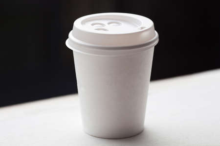 Disposable coffee cup on windowsill with city in background. Stock Photo - 33611531