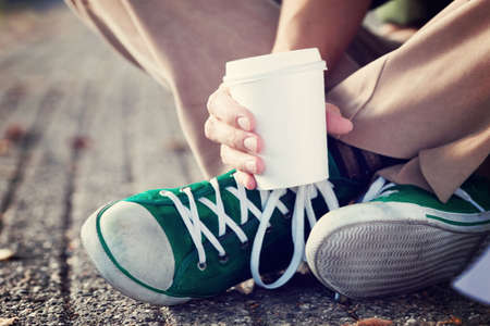coffee to go: Young woman drinking coffee from disposable cup