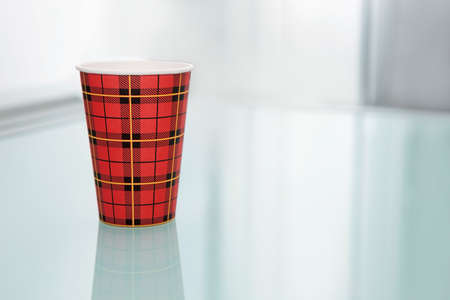table glass: Disposable coffee cup on the glass table.