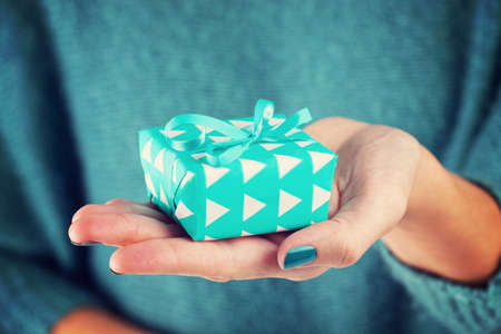 wedding wishes: Close-up of female hand holding a present Stock Photo