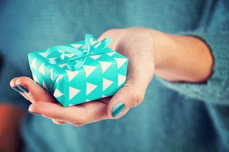 dar un regalo: Primer plano de la mano femenina sosteniendo un regalo Foto de archivo