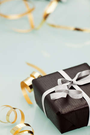Black gift box with silver bow on light background. photo