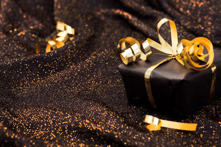Black gift box on black shiny background. Stock Photo