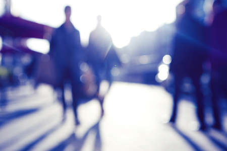 busy street: City commuters. High key blurred image of people walking in the street. Unrecognizable faces.