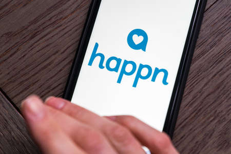 Young woman holding a smartphone with Happn dating app on screen. IPhone 11 with a social media chatting and meeting new people app logo.