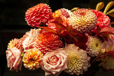 Floral composition of dahlia flowers, roses and autumn leaves. Arty, bright red and pink color bouquet of flowers on gray concrete background