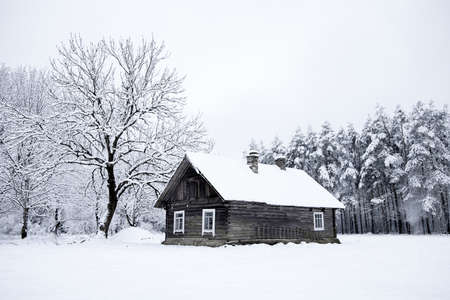 Nice old village house in the middle of beautiful winter with lots of white snow and trees. Christmas magic, winter tale with white fields. Archivio Fotografico