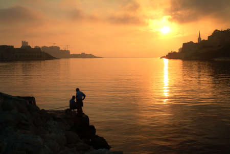Silhouette of fishermen at sunrise, Malta, Europe. Stock Photo - 683000