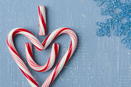 Candy Cane Heart Symbol on Blue Wood with Snowflake photo