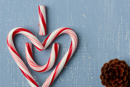 Candy Cane Heart Symbol on Blue Wood with Pinecone photo