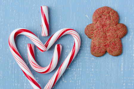 Candy Cane Heart Symbol on Blue Wood with Gingerbread Man Cookie photo