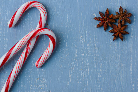 Candy Canes and Anise on Light Blue Wood Background photo