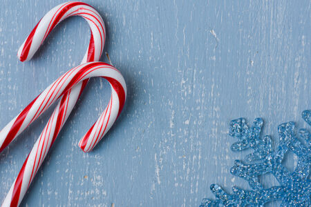 Candy Canes and Blue Snowflake on Light Blue Wood Background photo