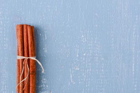 Cinnamon on Blue Wood with Pinecones photo