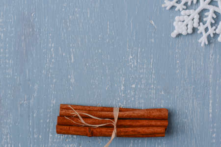 Cinnamon and Snowflake on Blue Wood with Pinecones photo