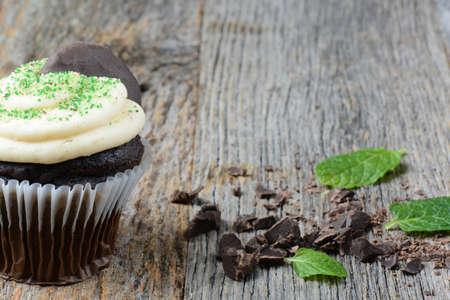 木製の背景に新鮮なミントの葉とミントのカップケーキ