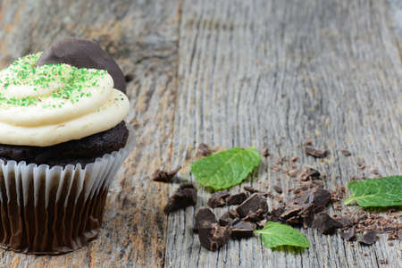 fattening: Mint Cupcake With Fresh Mint Leaves on Wooden Background