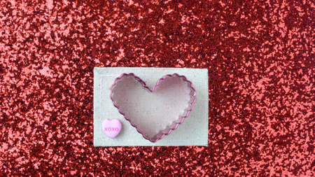 cookie cutter: Hearts on Red Glitter Background With Cookie Cutter and Candy