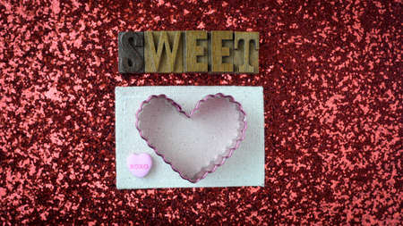 wood cutter: Wood Blocks Spelling the Word Sweet with Hearts on Red Glitter Background With Cookie Cutter and Candy