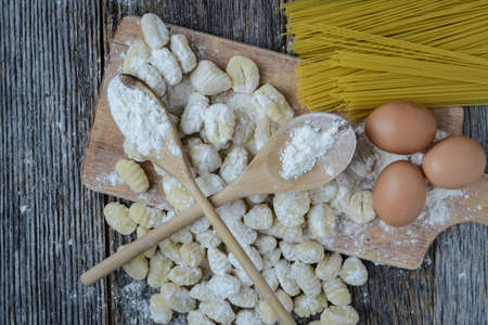 Gnocchi on Cutting Board and Rustic Wooden Background photo