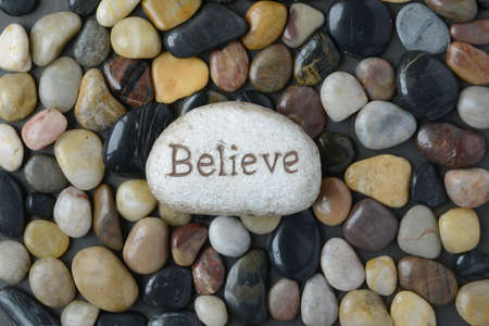single word: Flush Pebble Stone and River Background with the word Believe on single larger rock Stock Photo