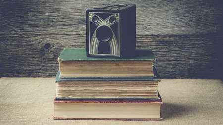 books and camera on retro background with Instagram Style Filter