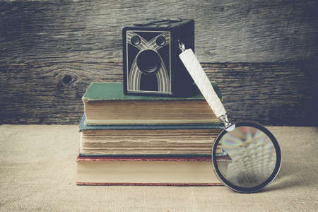 emigranti: libri, macchina fotografica, e lente di ingrandimento su sfondo retr� con stile Instagram Filter