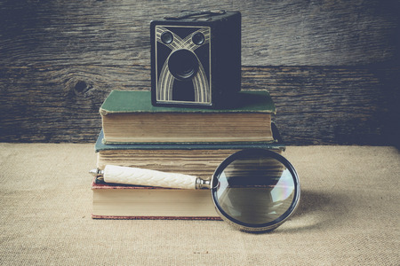 books, camera, and magnifying glass on retro background with Instagram Style Filter