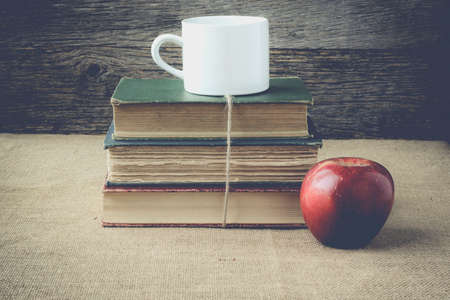 books and apple  with coffee cup on retro background with Instagram Style Filter