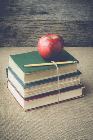 books and apple  on retro background