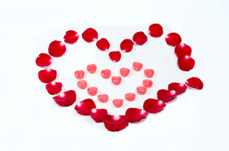 valentinas: red candy hearts with rose petals isolated on white
