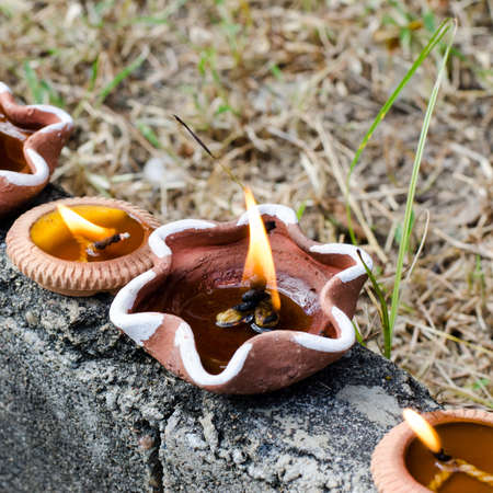 Burning candle in brick pots photo