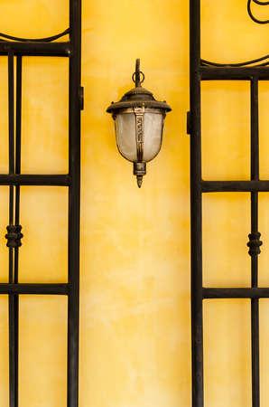 Lantern on a yellow wall photo