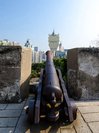 cast in place: Old cannon and new casino building, Macau Editorial