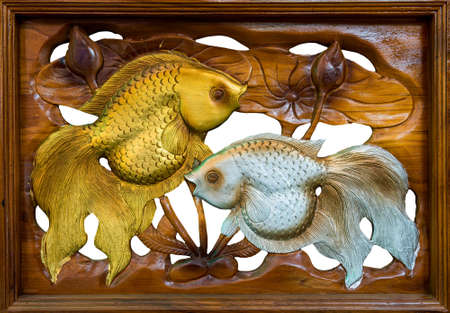 Fish wooden carving isolated on white background photo