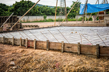 reinforcing: floor area covered in a sheet of plastic and a mesh of steel reinforcing rods
