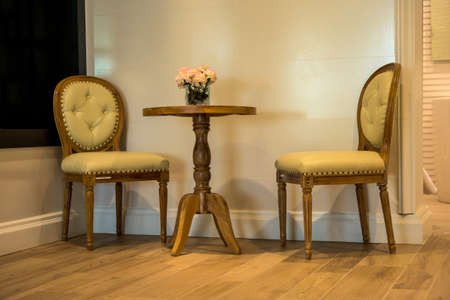 side table: Retro tan leather chair and side table with flowers interior Stock Photo