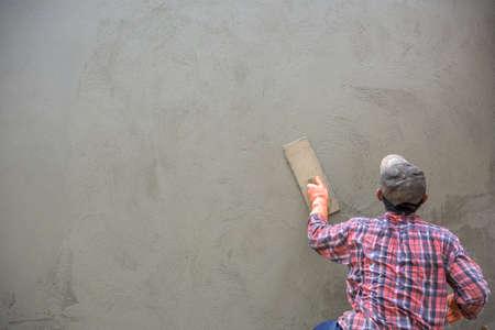Arbeider van de bouwer het pleisteren beton bij muur