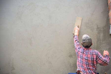alba�il: Trabajador del constructor enlucido de cemento en la pared