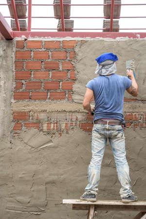 constructor: Trabajador del constructor enlucido de cemento en la pared