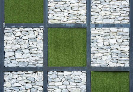 Wall of stone and artificial grass background.
