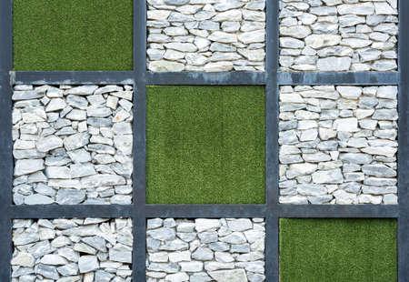 Wand aus Stein und künstlichen Gras Hintergrund.