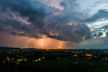 powerful: High angle view of Storm and lightning over villages