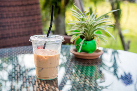 iced coffee: iced coffee and plant pots on the table. Stock Photo