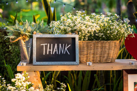 Thank you blackboard sign with red heart and basket of flowers