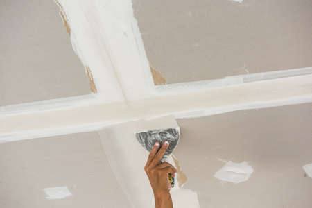 ceiling: man hand with trowel plastering a ceiling, skim coating plaster walls