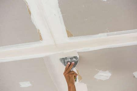 mano del hombre con una llana de techo, paredes de yeso de revestimiento descremada
