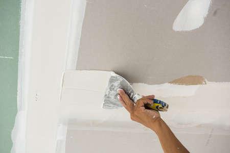 skim: man hand with trowel plastering a ceiling, skim coating plaster walls